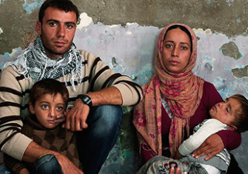 A refugee family with two young sons in a room on the border between Syria and Turkey.